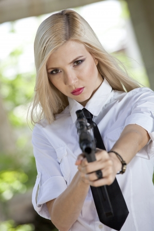 angry woman in white shirt and tie aiming the gun in the camera photo