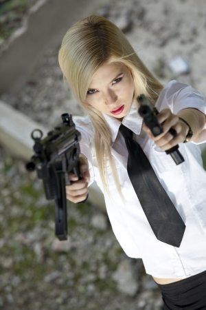 angry young woman with two guns aiming in the camera photo
