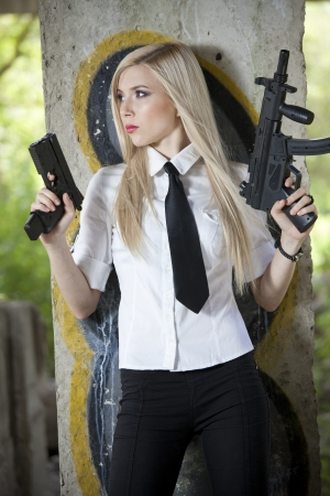 female spy in shirt and tie with two guns standing at the wall photo