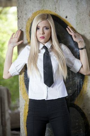 young woman in shirt and tie standing at the wall in surenderring pose - fear expression