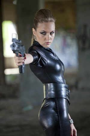 young woman in fetish leather suit holding a gun photo