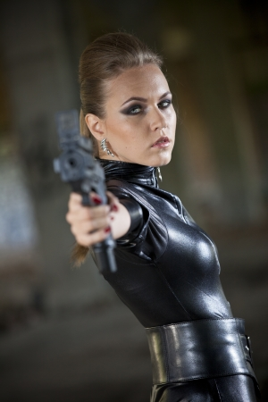 woman in leather catsuit aiming with a gun in the camera photo