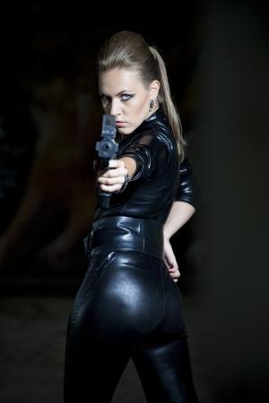 mujer con pistola: Mujer arma en juego de cuero negro sobre Foto de archivo