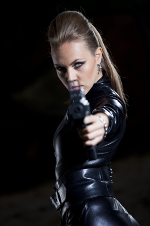 shiny suit: woman with gun in leather suit over black aiming at the camera