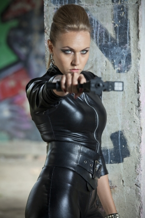 serious woman in leather outfit holding a handgun, standing at the wall in old ruins