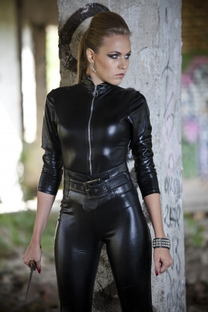 fetish: sexy woman in a leather catsuit holding combat knife in old fabric ruins