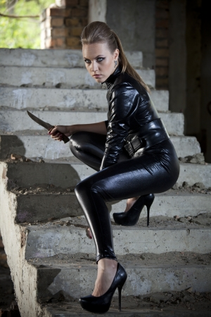 woman playing a spy in leather catsuit, holding a combat knife in fighting pose on stairs Stock Photo
