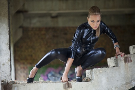 spies: woman in leather catsuit and heels holding combat knife in a fighting scene, posing on stairs in old fabric Stock Photo