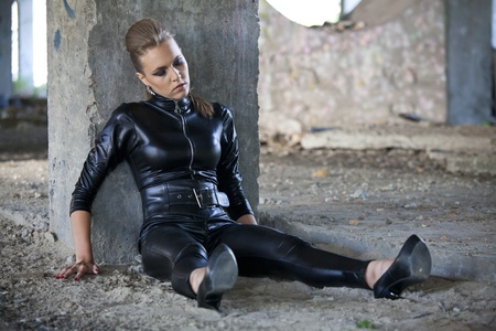 woman in leather suit sitting unconscious or sleeping on the ground, playing a crime scene photo