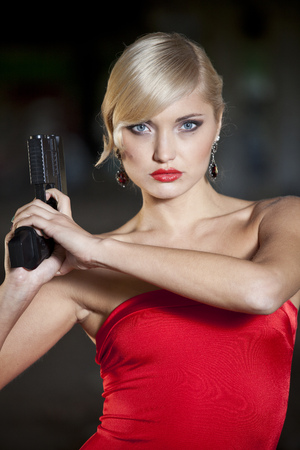 woman in retro look and red dress holding a handgun photo