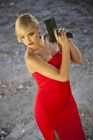 Beautiful assassin in red dress with gun playing a spy Stock Photo