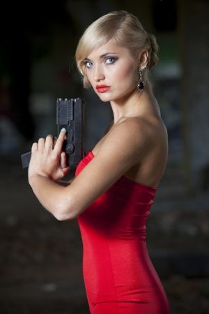 Spy woman in retro look holding a gun photo