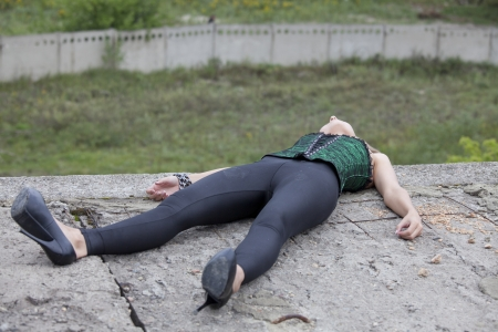 Crime scene - young woman in black leggings lying unmoving on the house roof Stock Photo