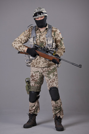 Soldier with sniper rifle posing over grey background photo