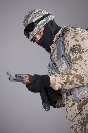 Soldier in camouflage awith kalashnikov machine gun in a studio photo