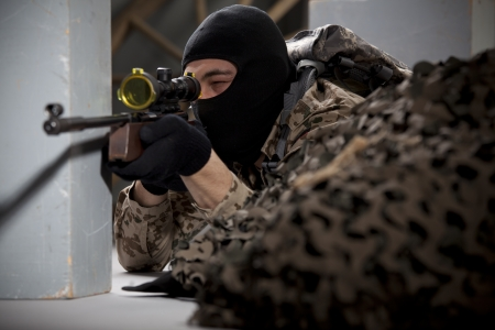 Spiner - soldier in camouflage and balaclava aiming with a sniper rifle photo