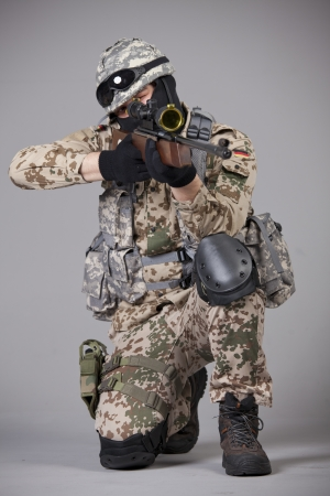 Sniper with rifle aiming over grey background photo