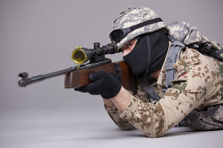 Sniper aiming - military scene shot in a studio over grey background photo