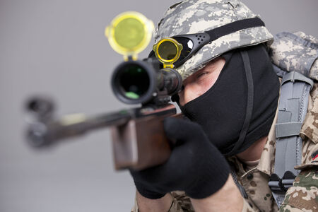 Sniper aiming and shooting - military scene making in a studio photo