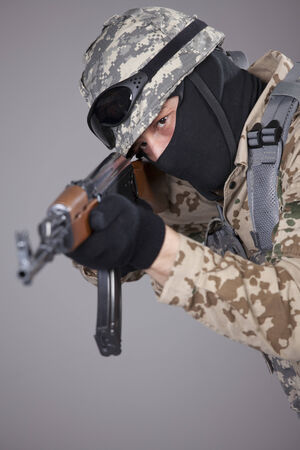 Russian soldier with kalashnikov machine gun aiming or shooting - shot in studio over grey background photo