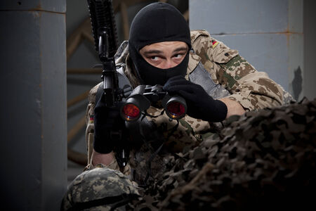 Special forces soldier with machine gun and binoculars hiding photo