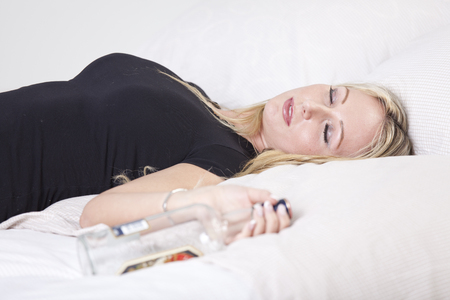 Drunk woman lying on bed, holding a bottle of alcohol Stock Photo