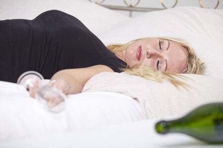 Drunk woman with glass, sleeping on bed Stock Photo