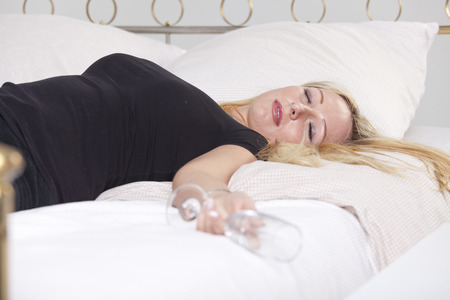 Drunk woman in black shirt with glass, sleeping in bed Stock Photo