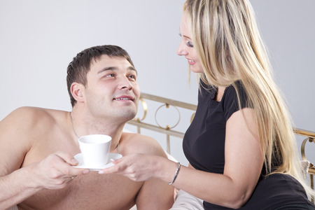 couple drinking coffee lying on their bed - shot in studio photo