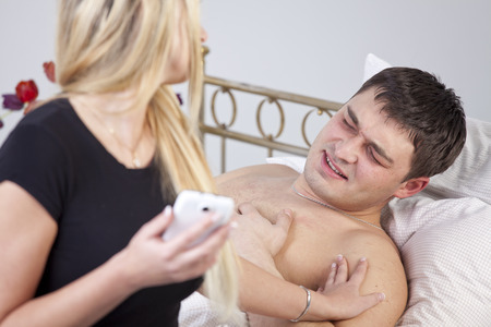 Sick man with ache on bed, worried woman holding phone at his side  photo