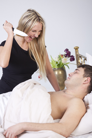 Angry wife with knife wants to kill her sleeping husband on bed - Jealousy scene photo