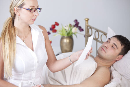 Woman reading medical report in front of sick man on the bed photo