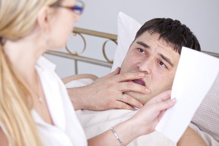 Shocked man on bed after a medicine report photo