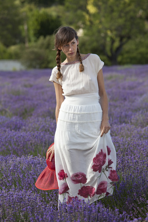 woman in a white dress with hat posing in a lavender field. photo
