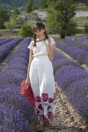 shy woman in white dress posing in a lavender field. photo
