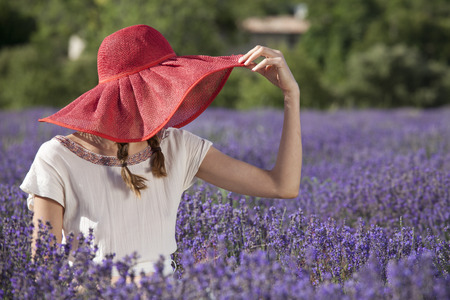 woman wearing white dress and hat sitting in a lavender field. photo