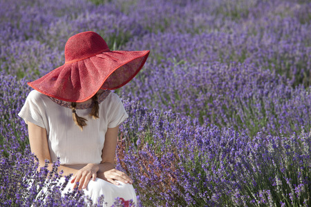 Portrait of sitting woman in the field of blossoming lavender photo