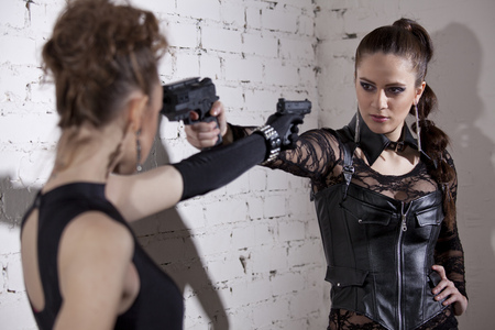 aiming: Two gangster women menacing each other Stock Photo
