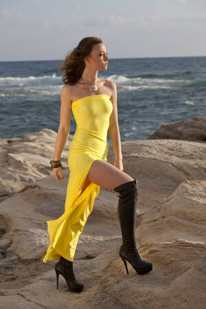 knee boots: Young Woman in yellow dress and over knee boots on the rocky beach