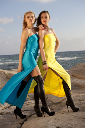 knee boots: Two young women in long evening dresses in over knee boots posing on the rocky beach Stock Photo