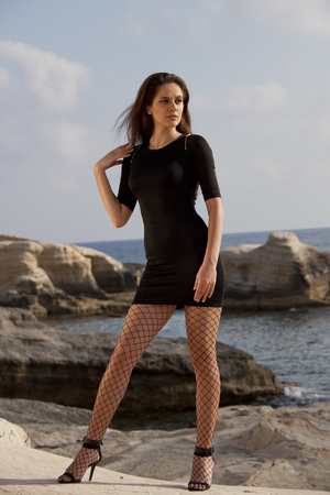 Woman in short black dress, fishnet pantyhose and high heels posing on rocky beach