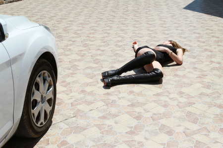 corpse: Car accident with woman lying unmoving on the ground
