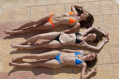 Three young women sunbathing on the marble floor near swimming pool. Stock Photo