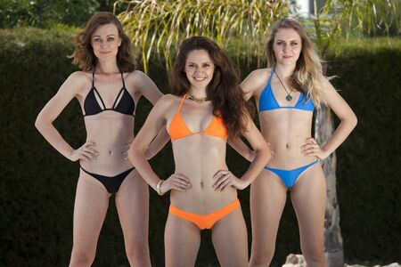 Three smiling fitness bikini girls posing by the swimming pool