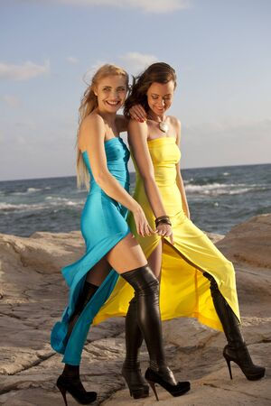 knee boots: Two happy young women in long evening dresses and over knee boots posing on the rocky beach