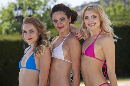 attired: Three happy woman attired in tiny bikinis looking in the camera Stock Photo