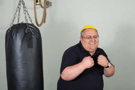 Fat man struggling with a punching bag in the gym Stock Photo