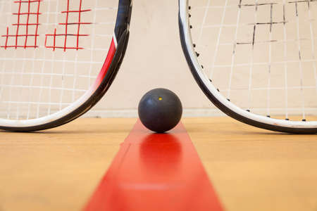 squash ball between two squash rackets on the court Stock Photo