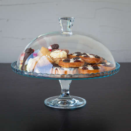 indulgence: cakes and sugar in a glass doze on black wooden table