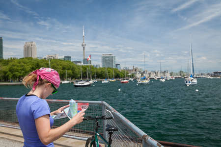 the right path: Tourists on the bike to find the right path on the map of Toronto, Canada